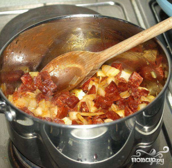 2.Разогреть масло в кастрюле на среднем огне и жарить чоризо, лук и чеснок приблизительно 4 минуты. Часто помешивать во время приготовления, чтобы все ингредиенты равномерно приготовились. Когда ингредиенты будут готовы, не убирайте оливковое масло. Оно добавит вкуса.