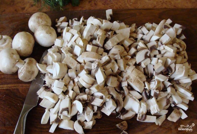 Лук выложите на горячую сковороду и обжаривайте на растительном масле. Пока лук жарится, нарежьте промытые грибы мелкими кусочками или тонкими пластинками.