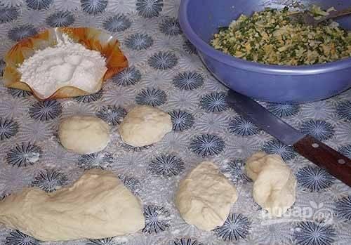 8. После второго подхода можно начинать лепить пирожки. Отщипните кусочек теста, разровняйте и выложите в центр начинку.