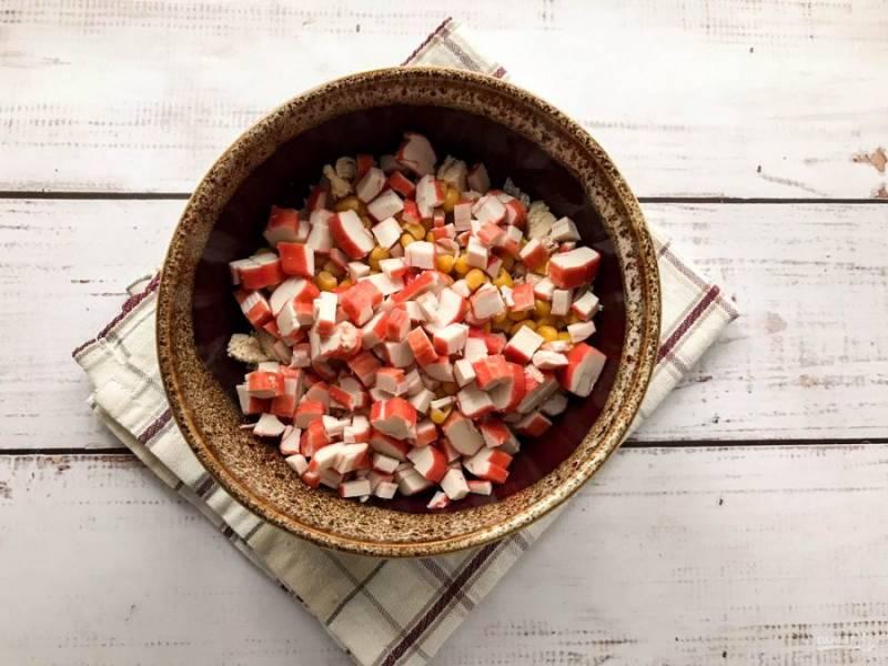 Крабовые палочки мелко нарежьте и высыпьте в тарелку к остальным ингредиентам.