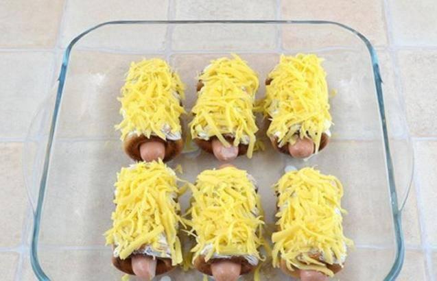 Посыпаем сосиски тертым сыром и отправляем в нагретую до 180-200 градусов духовку минут на 15-20.