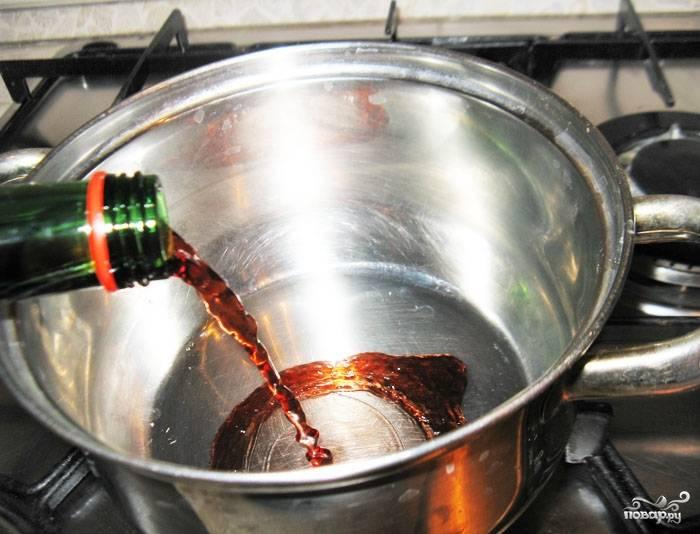 В кастрюлю налить вино и поставить на средний огонь.