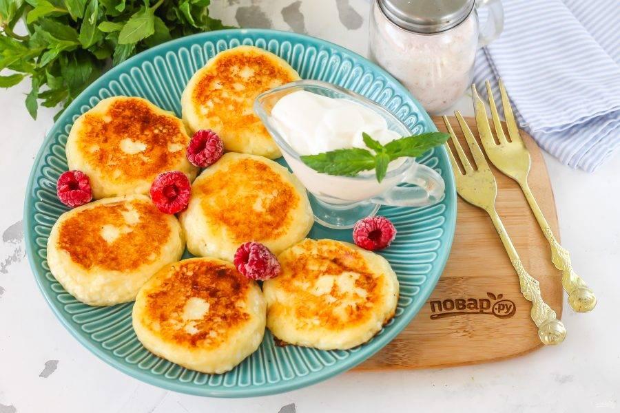 Выложите сырники на тарелку и подайте к столу горячими с классическим йогуртом, ягодами или сухофруктами.