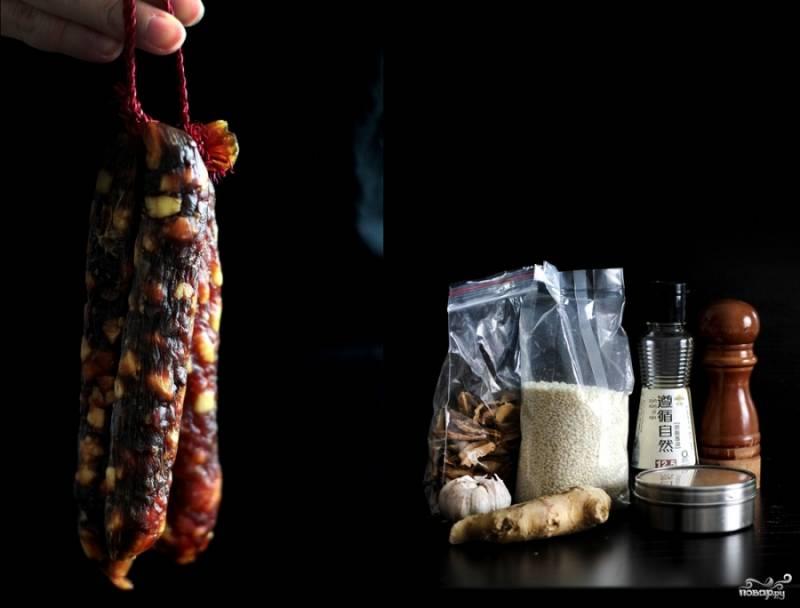 Подготовьте ингредиенты для начинки. Рис отварите, но не совсем до готовности. Колбасу порежьте колечками, грибы сухие залейте водой сначала. Обжарьте колбасу, затем добавьте грибы и перемешайте. Отварной рис добавьте к колбасе и грибам. Вода, что осталась от замачивания белых сушеных грибов, пригодится в тушении: влейте где-то треть стакана и протушите все минут 15. Добавьте смесь специй, измельченный чеснок, тертый имбирь, соевый соус и соль по вкусу. Готовьте еще минут 10-15.