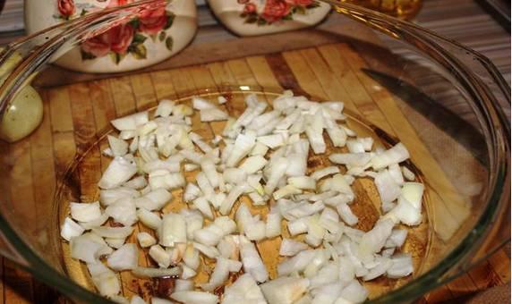 1. Форму для запекания смажем маслом и выкладываем первым слоем измельченный лук на дно.