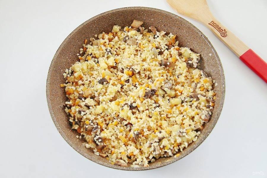 Добавьте булгур, соль, перец по вкусу, перемешайте и потушите начинку около 5 минут.