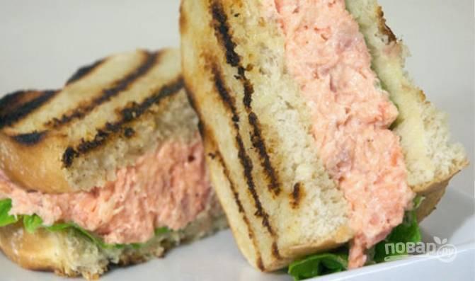 Салатные листья промойте и обсушите, выложите на хлеб. Сверху уложите пасту из рыбы и прикройте вторым ломтиком хлеба. Разрежьте по желанию.