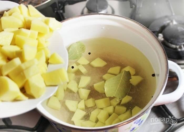 1.Картошку очистите и нарежьте небольшими кусочками. В кастрюлю налейте воду и добавьте лавровый лист, щепотку соли и пару горошин черного перца. Отправьте кастрюлю на огонь и доведите до кипения, отправьте в нее картофель.
