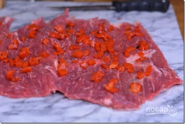 Болгарский перец промойте, порежьте мелким кубиком и обжарьте на сковороде до золотистого цвета. Равномерно разложите перец по всей поверхности мяса.