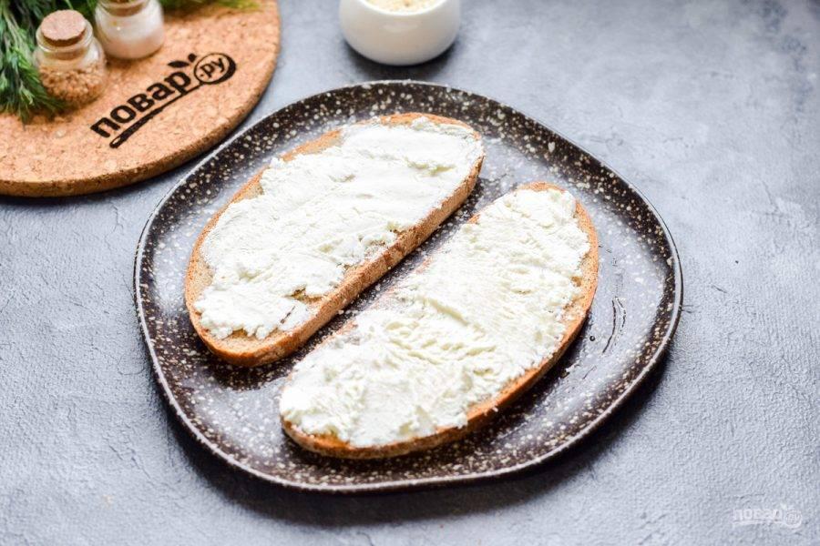 По желанию ломтики хлеба можно подсушить на сковороде или в духовке. Смажьте хлеб творожным сыром. Выбирайте нежирный сыр, можно взять с травами или зеленью.