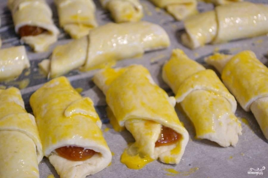 Рогалики уложите на противень с пергаментом для выпечки. Смажьте их взбитым желтком.
