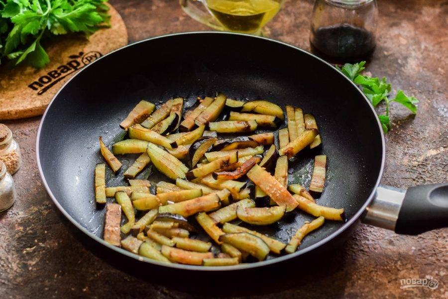 В сковороде прогрейте растительное масло, выложите баклажаны и жарьте несколько минут до румяности.