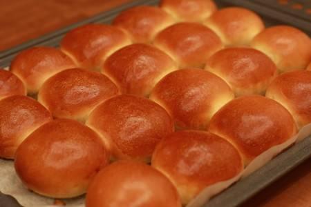 Выложите булочки на противень, предварительно смазанный растительным маслом.  Разогрейте духовку до 200-210 градусов. Выпекайте булочки примерно 25-30 минут. Готовые горячие булочки со сгущёнкой можно подать к чаю. Приятного аппетита!
