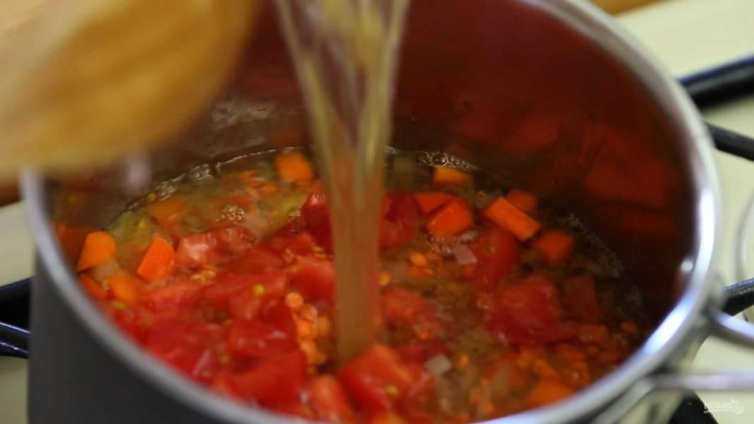 3. После этого добавьте промытую чечевицу, нарезанные помидоры и томатную пасту, а также влейте бульон.