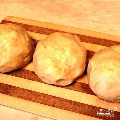 Хорошенько смешав все ингредиенты, кладем смесь на присыпанную мукой рабочую поверхность и месим тесто. Получившееся тесто делим на 3 равные части, каждую из которых скатываем в шарик. Ставим наши шарики в морозилку на 20-25 минут.
