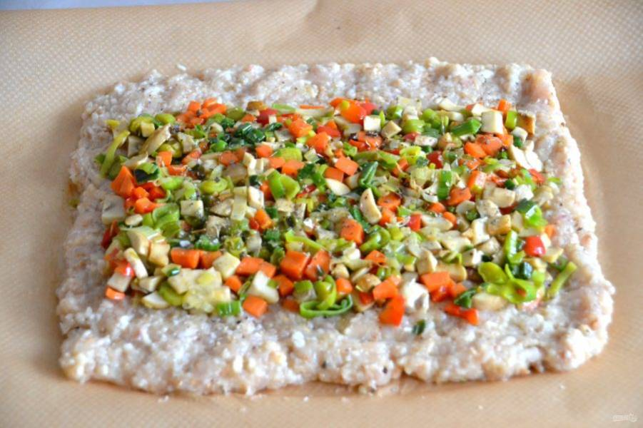 Выложите в центр прямоугольника из куриного фарша овощную смесь, отступая от краев примерно по 5 см. Присыпьте сухими пряными травами.