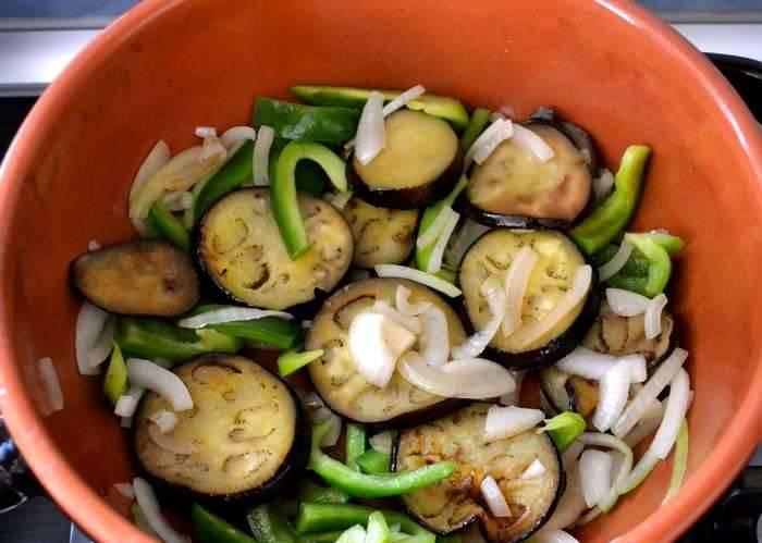 1. Баклажаны нарезаем тонкими кружочками, обжарим с двух сторон на растительном масле, по 5-6 минут с каждой. Затем добавим измельченные перец и лук. Обжарим, пока овощи не станут мягкими, еще минут 6-7.