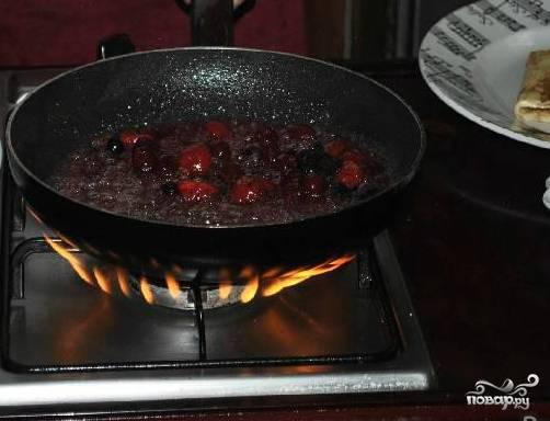 В оставшуюся карамель выкладываем ягоды вместе с кусочками сливочного масла. Тушим, переворачивая ягоды легким движением руки. Доливаем коньяк и поджигаем.