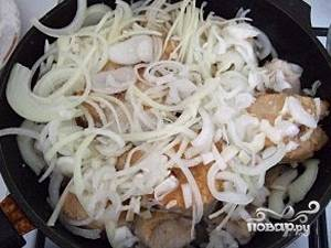 Затем в сковородку равномерно добавляем лук. Лук должен закрыт всю рыбу.