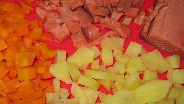 2. Тем временем начинаем чистить рыбу. Нарезаем ее кубиками небольшого размера. Когда остынут овощи, также шинкуем их кубиками.
