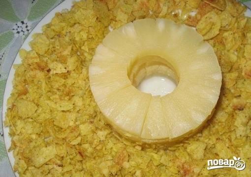 Чипсы превратите в крошку и выложите на блюдо. Очистите чеснок и измельчите его при помощи ножа или пропустите через специальный пресс. Смешайте чеснок с майонезом. Смажьте слой чипсов чесночным соусом.