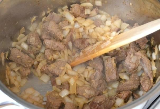 3. Теперь отправляем мясо жариться на сковороду и в середине добавляем лук. Нарезать его можно как пожелаете. Обжариваем мясо до легкого золотистого цвета, добавляем сметану и заливаем водой. Вот и все, теперь накрываем крышкой и тушим около получаса на слабом огне.