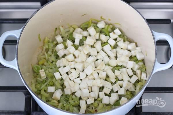 6. Добавьте нарезанный корень сельдерея и влейте заранее приготовленный бульон или воду.