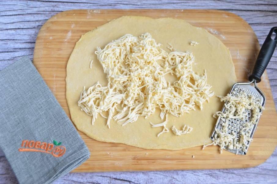 8. Тесто раскатайте до тончайшего состояния в прямоугольный пласт. При необходимости стол и тесто при раскатывании можно подпылять мукой. Прямо на раскатанное тесто натрите плавленый сыр.