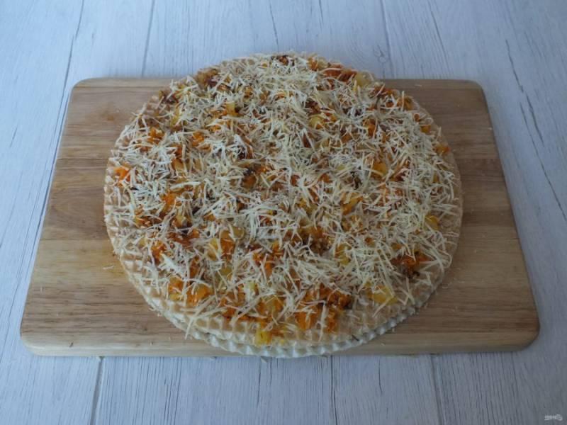 Положите сверху второй вафельный лист. На нем разложите обжаренные лук с морковью. На овощи натрите 1/2 часть указанного количества сыра.