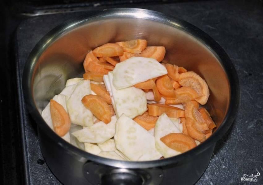 Очистите морковь и сельдерей, а затем нарежьте их крупными дольками. Эти овощи слегка обжарьте в сотейнике на растительном масле. Овощи должны стать мягкими.