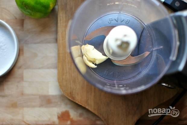 2. В чашу блендера отправьте очищенный зубчик чеснока.