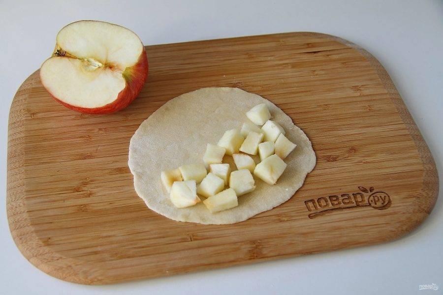 На подпыленной мукой поверхности раскатайте каждую часть теста в форме круга, толщиной 2-3 мм. Яблоки очистите, нарежьте кубиками и положите начинку на один край.