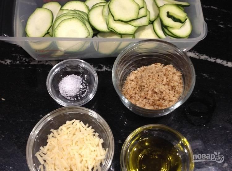 1.Вымойте цуккини, нарежьте тонкими кружочками. Натрите на крупной терке сыр. Разогрейте духовку до 220 градусов.