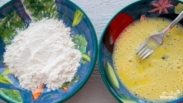 Приготовьте две чашки, в одной взбейте яйца, в другую высыпьте муку.