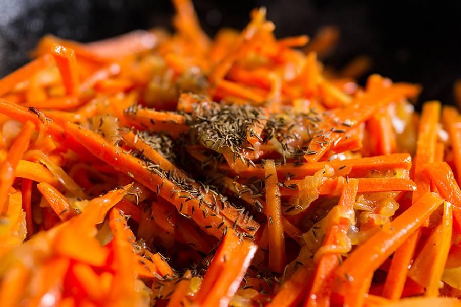 Натираем на терке морковь и добавляем в казан, сверху присыпаем зирой. Готовим под крышкой на среднем огне, примерно 20 минут.
