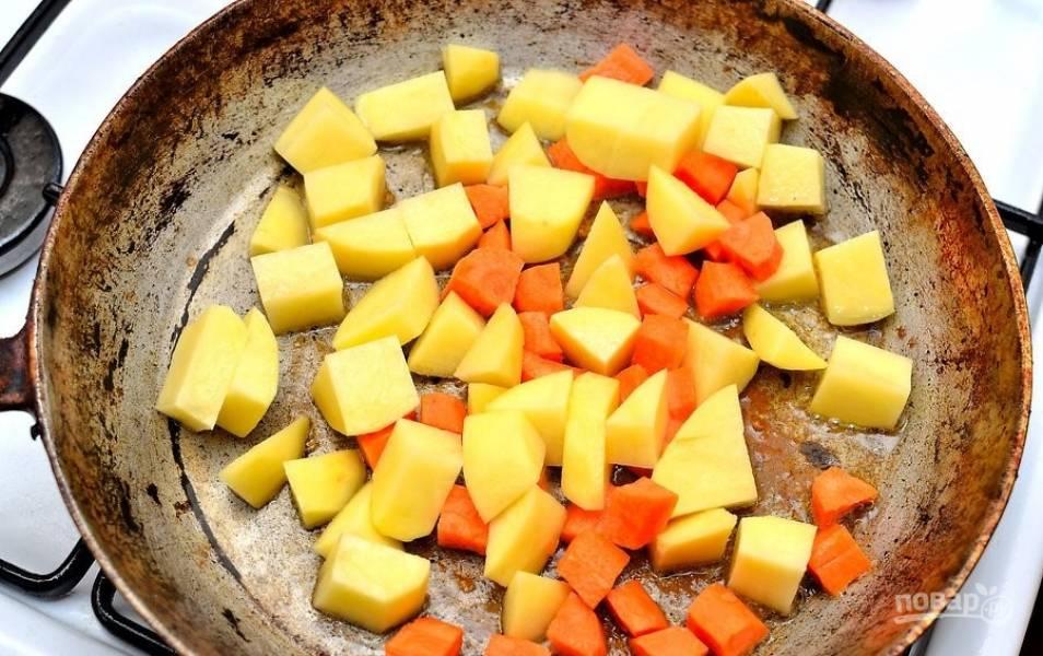 Промойте и почистите овощи. Лук нарежьте мелко, а картофель и морковь крупными кусочками. Утку со сковороды достаньте и выложите овощи.