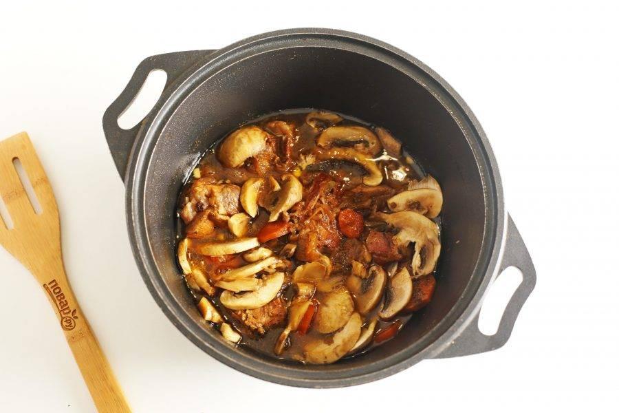 Затем добавьте нарезанные шампиньоны и чеснок. Оставьте кролика с грибами и овощами в казане еще на 20 минут потомиться.