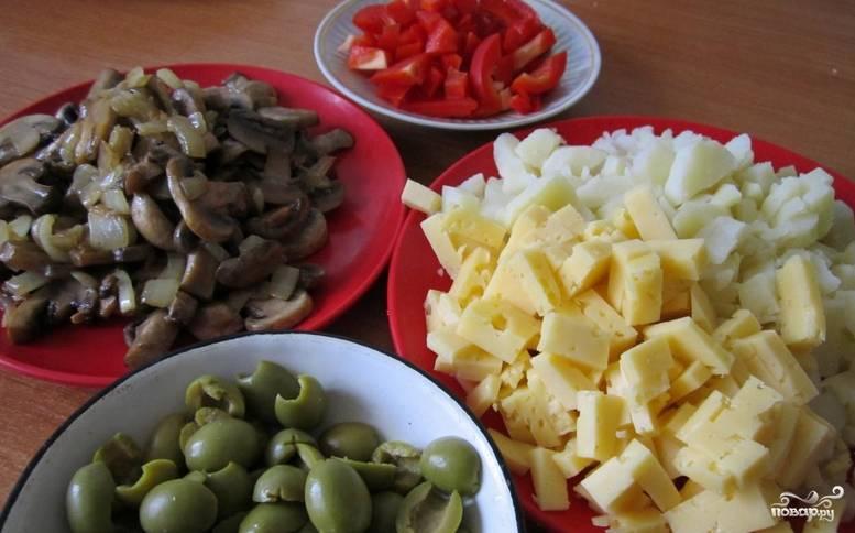 Предварительно отварите картофель, затем остудите и мелко нарежьте его. Шампиньоны нарезаем пластинками и обжариваем на сковороде до готовности вместе с репчатым луком. Перец очищаем и нарезаем кубиками, таким же образом нарезаем твердый сыр. Оливки разрезаем пополам.