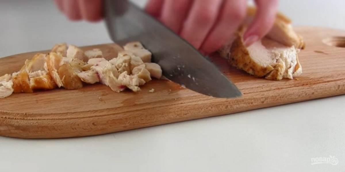 1. Куриное филе натрите солью и специями. Обжарьте на сковороде с двух сторон на небольшом огне до готовности. Остудите и нарежьте филе кубиками.