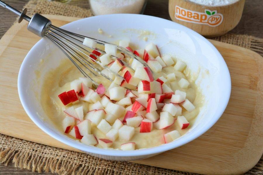 Добавьте в тесто нарезанные кубиками яблоки.