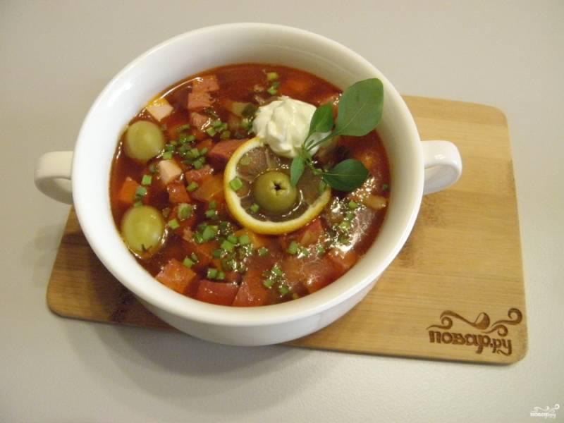 Наливайте солянку в глубокие порционные тарелки, посыпайте рубленой свежей зеленью, добавьте ломтик лимона и оливки, сметану. Приятного!