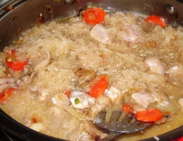 Добавьте промытый рис, перемешайте и протушите в течение 15 минут до испарения жидкости.