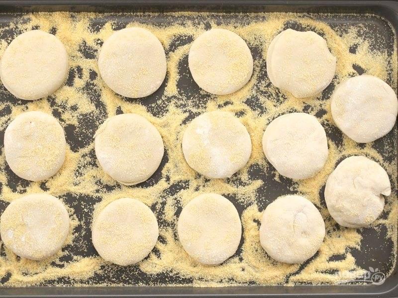 7.Посыпьте противень кукурузной мукой, выложите на него тесто, придавите, переверните и снова придавите, таким образом выпечка с двух сторон будет покрыта кукурузной мукой, благодаря этому она не прилипнет.