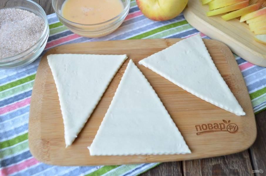 Вилочкой взболтайте яйцо. Разложите тесто, у меня получилось три полоски. Раскатывать его не нужно, ножом для пиццы порежьте на треугольники.