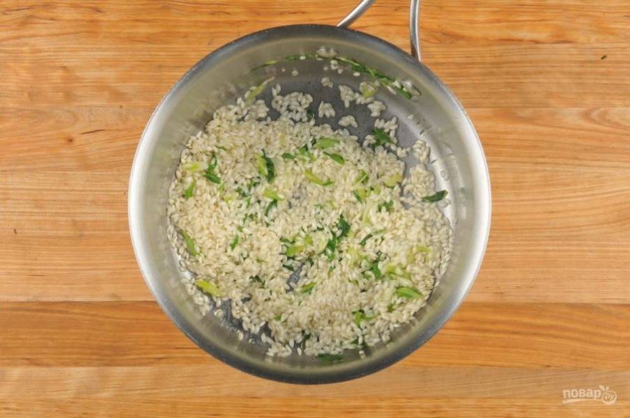3. Тем временем в сотейнике обжарьте в течение 2 минут промытый рис в оливковом масле вместе с луком и солью. Затем к нему влейте вино. Готовьте ещё 2 минуты, постоянно помешивая.