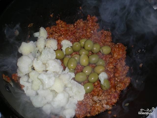 Теперь в глубокую сковороду или в казан наливаем оливковое масло и жарим на нем лук и чеснок до золотистого цвета. Выкладываем фарш, солим и перчим, тушим в течение 5 минут на среднем огне. Затем добавляем томатную пасту, перемешиваем и еще 10 минут тушим все. Теперь очередь цветной капусты и оливок. Выкладываем их в сковороду, заливаем все горячей водой и готовим под закрытой крышкой на медленном огне примерно 25 минут. Получается очень вкусное и довольно красивое блюдо. Приятного всем аппетита!
