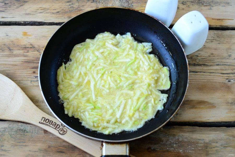 На сковороде разогрейте растительное масло. Ложкой выложите кабачковое тесто, распределите его слоем примерно в 3-4 мм по поверхности сковороды. Жарьте блины по 4-5 минут на минимальном огне до золотистого цвета.