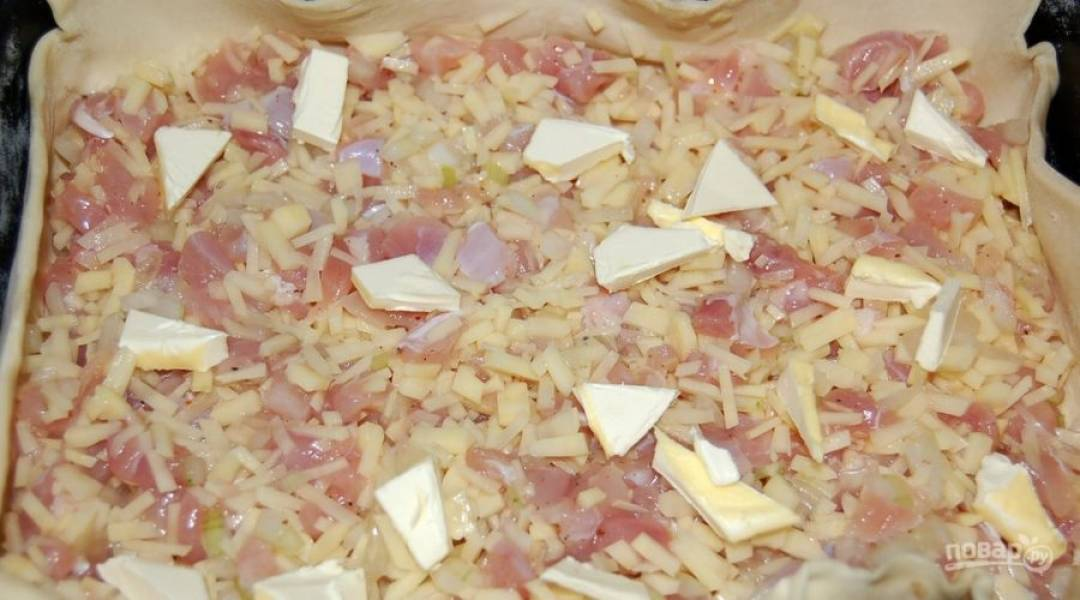 1.Очистите картошку и нарежьте тонкой и мелкой соломкой, репчатый лук измельчите. Сырое куриное мясо нарежьте кусочками. Смешайте подготовленные ингредиенты, посолите и поперчите, добавьте 2-3 ложки воды. Разделите слоеное тесто на 2 части. Раскатайте одну и уложите в форму для запекания, выложите начинку и добавьте кусочки масла.
