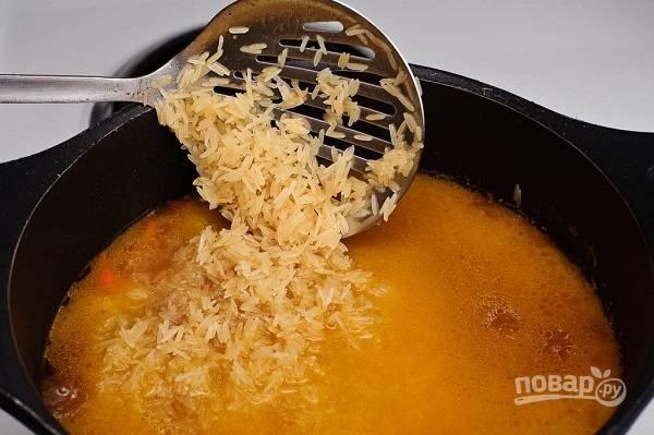 8. Промойте под проточной водой рис. Выложите его аккуратно в казан ровным слоем.