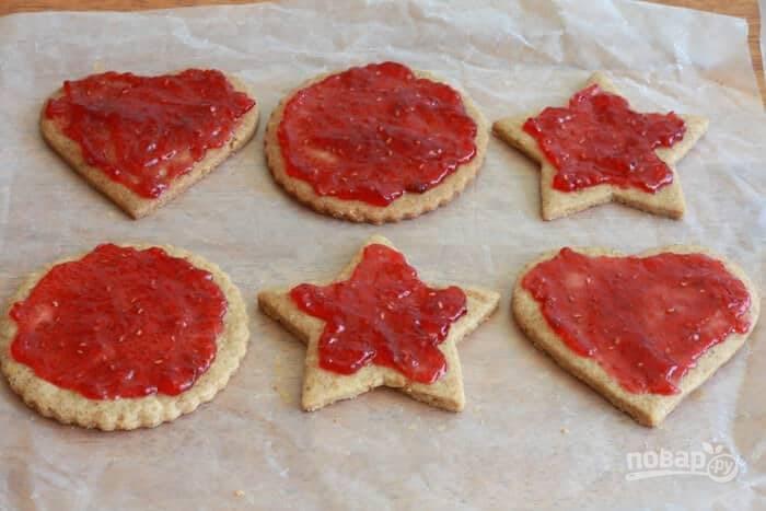 16.После остывания выложите печенье без дырочек внутри, смажьте его малиновым вареньем.